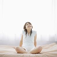 ベッドで胡坐をかく女性