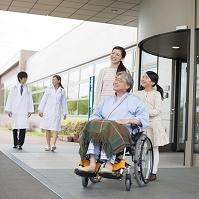 祖父の乗る車椅子を押す親子