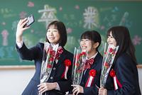 黒板の前で自分撮りをする女子学生