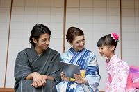 タブレットを見る浴衣の日本人家族