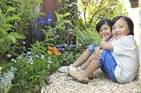 庭でかくれんぼをして遊ぶ日本人の女の子と男の子