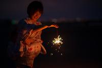 花火をする浴衣姿の若い女性