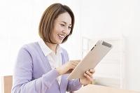 タブレットを操作するミドル女性