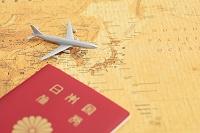 世界地図の上に置かれたミニチュアの飛行機とパスポート