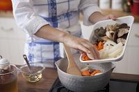 野菜を鍋に入れる女性