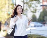 スマートフォンを片手に歩く日本人女性