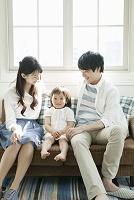 部屋で団らんの若い夫婦と子供