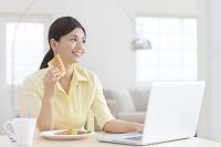 パソコンを見ながら朝食を食べる女性
