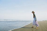 海辺にいる麦藁帽子をかぶった女性