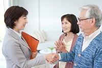 握手をするビジネス女性とシニア夫婦