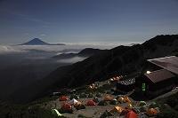 山梨県 南アルプス市 北岳から望む夜の富士山と雲海と野営テント