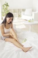 ベッドでボディケアをする若い日本人女性