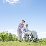 車椅子に乗る男性と介護する女性