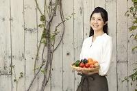野菜が盛ってあるザルを持つ日本人女性