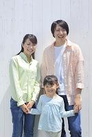 白い壁の前に並ぶ日本人三人家族