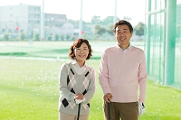 ゴルフ場に立つ熟年夫婦