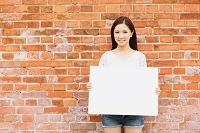 レンガの壁とホワイトボードを持つ日本人女性