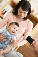 スマートフォンで写真を撮られる日本人親子