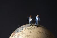 地球儀とビジネスマンのミニチュア人形