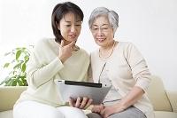 タブレットを見る母と娘