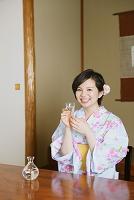 旅館で冷酒を飲む浴衣の日本人女性