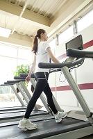 ランニングマシンで運動する女性