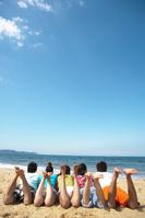 砂浜に並んで寝転ぶ若者達