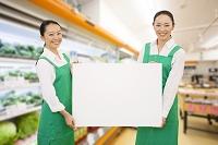 ホワイトボードを持つスーパーの店員の日本人女性