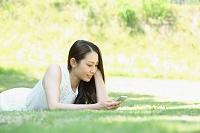 スマートフォンを手に公園でくつろぐ日本人女性