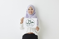 ハラールのロゴのパネルを持つムスリムの女性