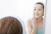 鏡でお肌をチェックする日本人女性