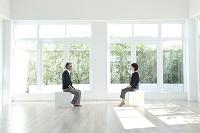 窓のある部屋に座るミドルカップル