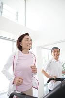 ジムで運動する中高年夫婦