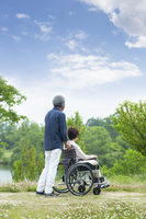 車いすで散歩する老夫婦