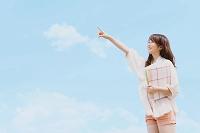 空と指を指す日本人女性