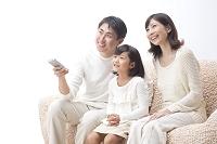 ソファに座ってTVを見ている日本人三人家族