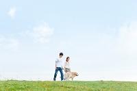 芝生を歩くカップルと犬