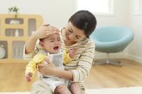 体調不良の赤ちゃんと熱を計るお母さん