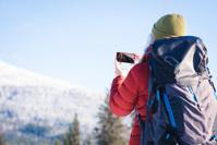 雪山でスマートフォンを使う女性