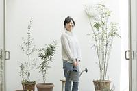 観葉植物に水やりをする日本人の若い女性