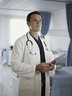 医療記録を持って病室に立つ医師