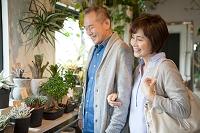 花屋で鉢植えを見る日本人シニア夫婦
