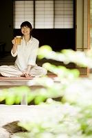 縁側に座りビールを持つ日本人女性