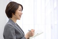 手帳にメモする日本人ビジネスウーマン
