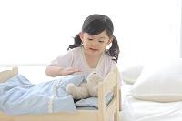 ぬいぐるみをおもちゃのベッドに寝かせて遊ぶ女の子
