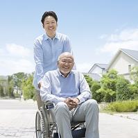 車椅子に乗る男性と介護する男性