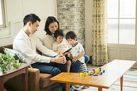 スマートフォンを見て団らんする仲良し日本人家族
