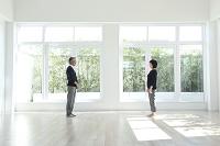窓のある部屋に立つミドルカップル
