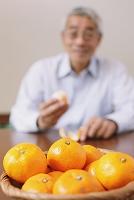 みかんを食べるシニアの日本人男性