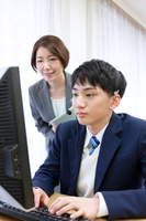 パソコンの指導をする教師と男子学生